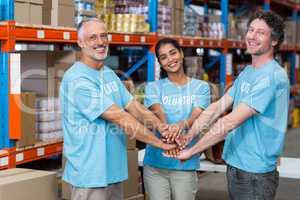 Portrait of happy volunteers putting hands together