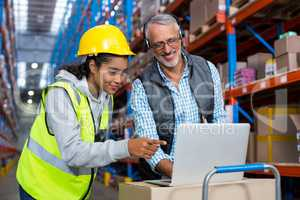 Warehouse manager and female worker using laptop