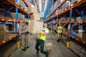 Worker losing his balance while carrying cardboard boxes