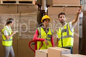 Warehouse workers discussing while preparing a shipment