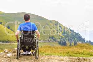 Young man in a wheelchair enjoying fresh air on a sunny day