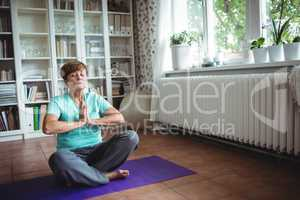 Senior woman meditating in prayer position