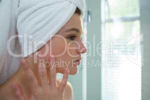Woman applying moisturizer cream on her face in bathroom