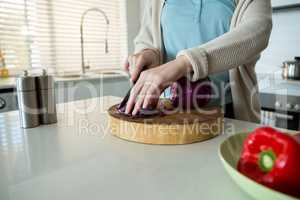 Mid section of woman cutting red cabbage in kitchen