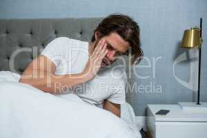 Man waking up from sleep in bedroom