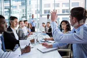 Colleague raising his hand during meeting