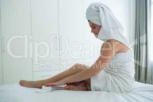 Woman applying moisturizer cream on her leg in bedroom