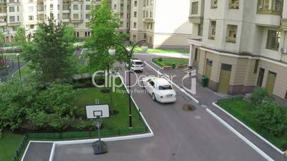 Two cars driving in the yard of multistorey houses, aerial view