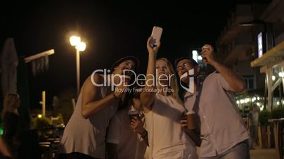 In evening in city of Perea, Greece young company taking selfies on a mobile phone
