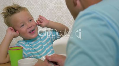 Son speaking with father and eat using a spoon and smiling