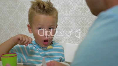 Father teaching son to use a spoon during eating