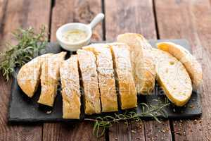 fresh homemade ciabatta bread sliced on stone slate board, olive oil and rosemary on wooden background