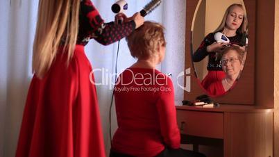 Daughter doing her elderly mother's hair