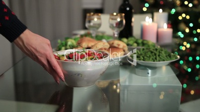 Woman serving bowl of salad on Christmas table