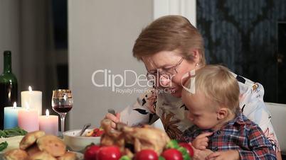 Loving grandmother feeding her grandson