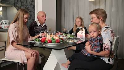 Family praying before thanksgiving meal