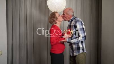 Senior man giving valentine's gift to his wife