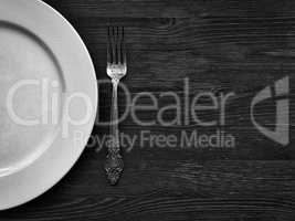 Empty white plate with a fork on a wooden surface, black and whi