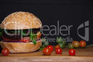 Tasty burger with meat cutlets served on a wooden board with che
