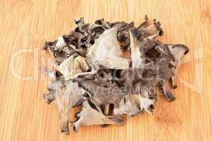 Heap of dried Horn of Plenty mushrooms on bamboo