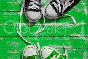 Two pairs of sneakers youth with untied laces on the green surfa