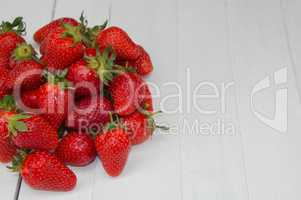 pile of ripe red strawberries on a white surface, empty space on