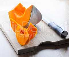 Sliced Pumpkin and knife on a wooden board