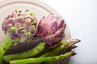 Artichokes and asparagus on a wooden board