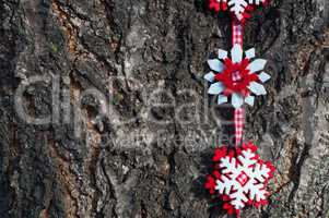 Snowflakes of felt on a red ribbon on a background of tree bark
