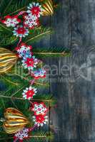 New Year and Christmas background with toys and spruce branches on a gray wooden background, top view