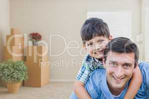 Father and Son in Room with Packed Moving Boxes and Potted Plant