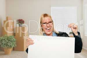 Woman with Blank Sign and House Key in Empty Room with Packed Mo
