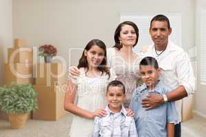Hispanic Family in Empty Room with Packed Moving Boxes and Potte