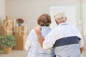 Senior Couple Facing Empty Room with Packed Moving Boxes and Pot