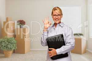 Woman with Okay Sign in Empty Room with Packed Moving Boxes