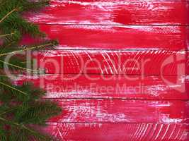 Red wood background with spruce branches on the right and an emp