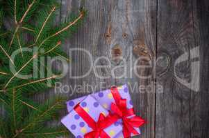 Gray wooden festive background with branches of spruce and packa