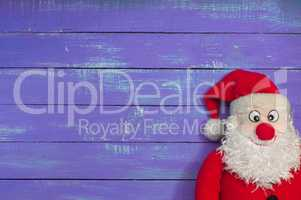 Cloth Santa Claus on a background of purple wooden surface