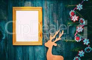 empty picture frame on a gray wooden surface with Christmas deco