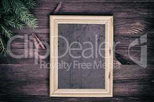 Vintage empty wooden frame with a branch of spruce in the corner