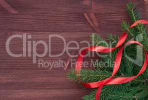 Branch with red ribbon on brown wooden background