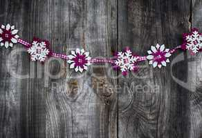 Fabric garland of snowflakes on a gray wooden surface, vintage t