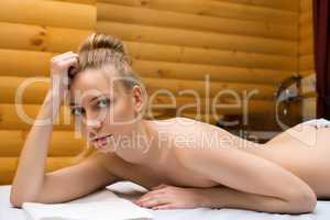 Beautiful naked girl posing lying in spa salon