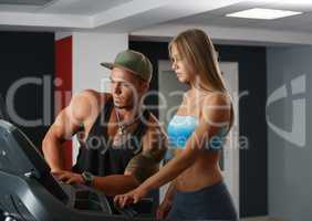 In gym. Instructor helps girl to set up simulator