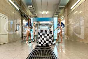 Car wash. Leggy girls posing with checkered flags