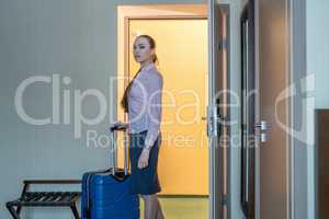 Hotel. Pretty woman with luggage entered into room