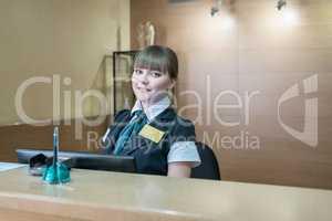 Hotel reception. Pretty hostess smiling at camera