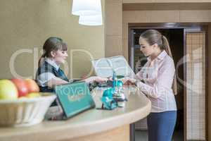 Businesswoman registers on arrival in hotel
