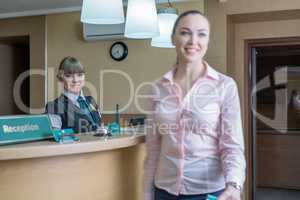 Hotel reception. Image of pretty hostess and guest