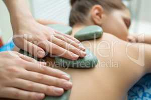 Massage therapist puts spa stones on girl's back